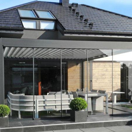 Pergola bioclimatique DETENTE à adossée lames perpendiculaires et sa façade vitrée coulissante fermée
